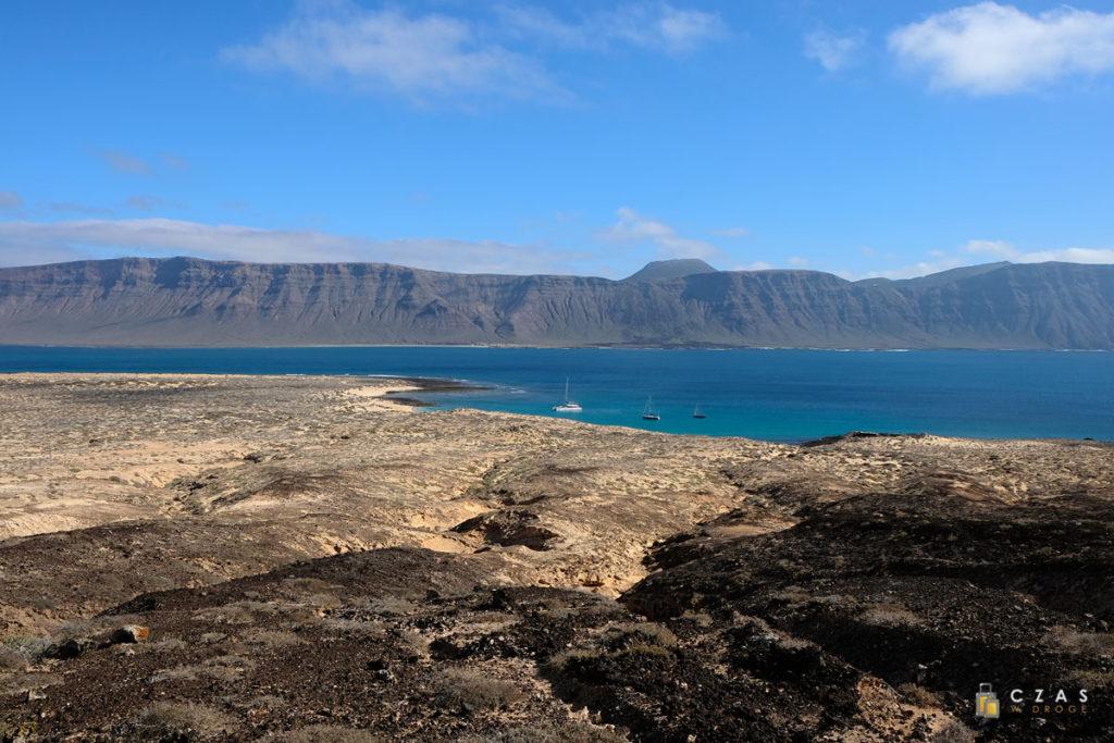 Piaszczysty krajobraz La Graciosy. W tle klify Lanzarote.